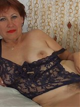 Sensual older woman Zina strips down in bed and shows her hairy pussy on webcam live
